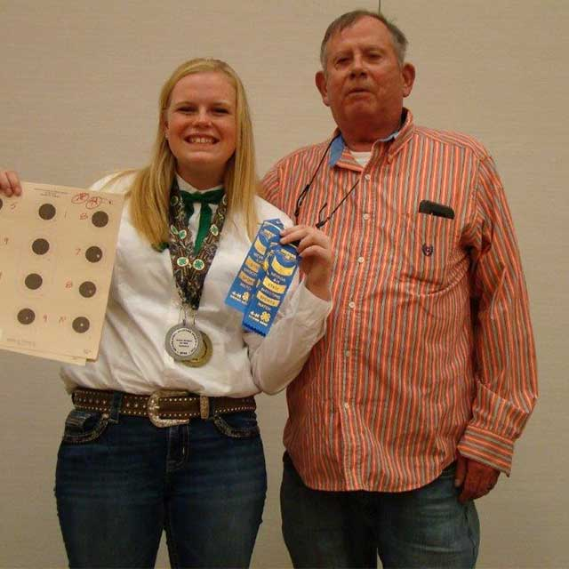 Tom Crowley with a 4-H'er who is holding her medals and ribbons