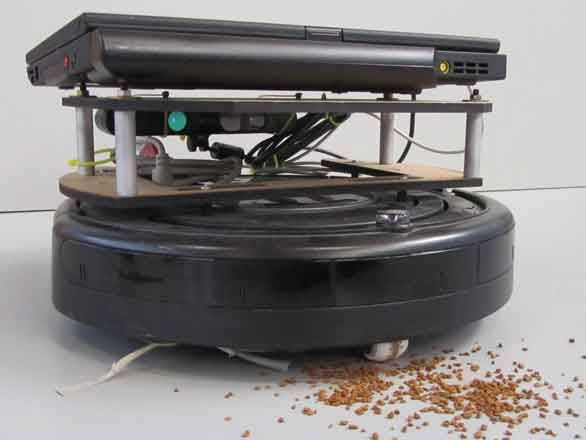 A robotic vacuum cleaner in front of a pile of crumbs