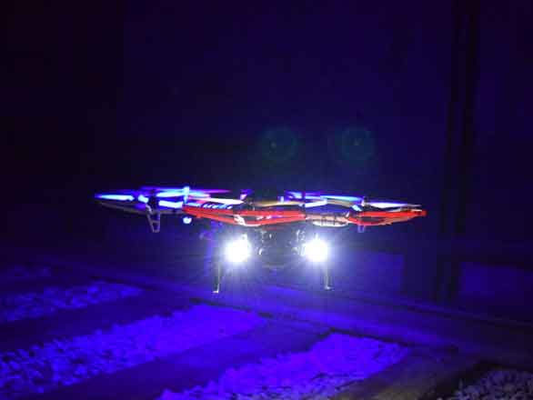 A lighted aerial robot flying over railroad tracks in a dark tunnel