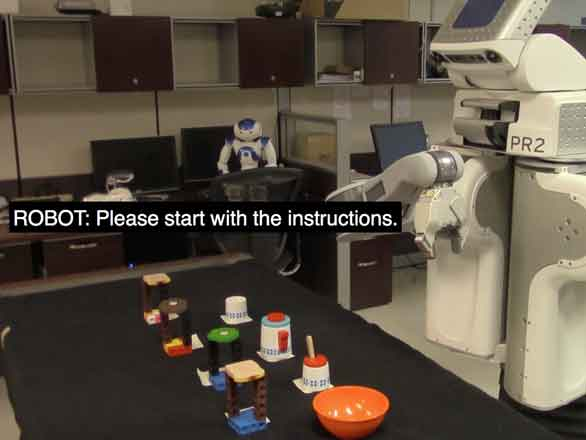 A PR2 robot in front of a table with a tea pot and cups. Caption text on the screen reads: ROBOT: Please start with the instructions.