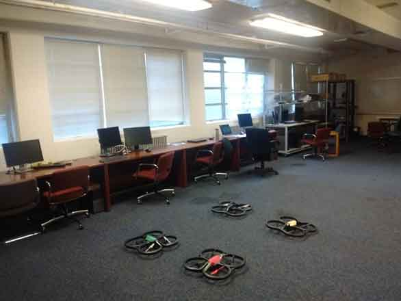 Four aerial robots on the floor in a carpeted lab