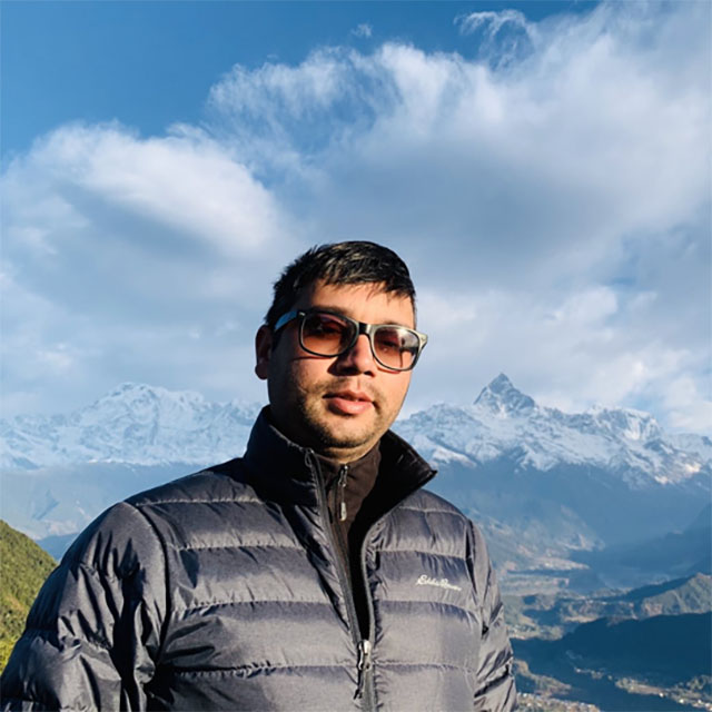 Saroj Dhital standing before a large mountain range, blue skies with white clouds.