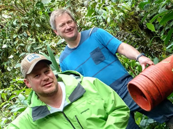 Two researchers smiling while working in the rainforest.