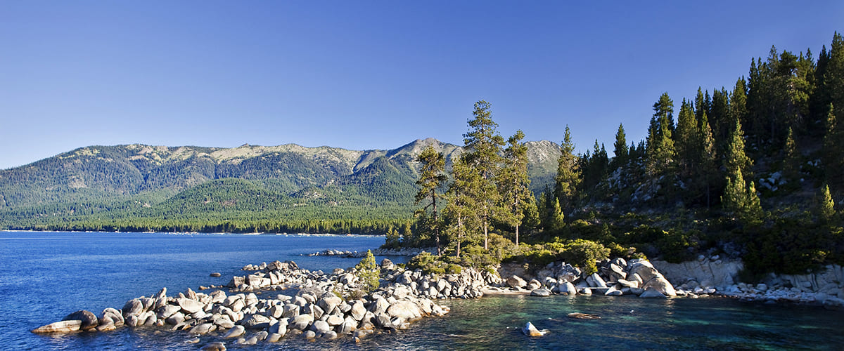 A view of Lake Tahoe, with forested mountains in the background and rocks spilling out in the lake