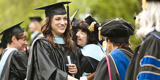 A master's student wearing Commencement cap and gown shaking hands with professors.