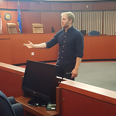 Student giving a speech to a mock jury in a courtroom.
