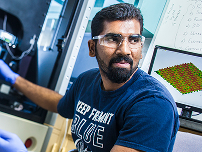 Graduate researcher working with engineering equipment and wearing eye protection.