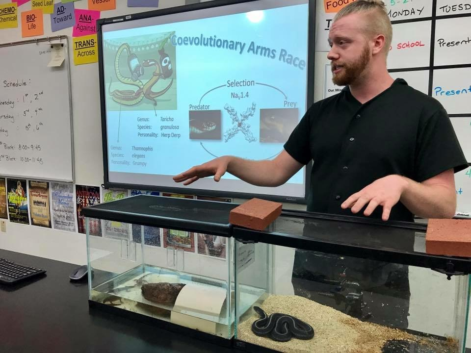 Student giving a lecture motioning to two terrariums with snakes.