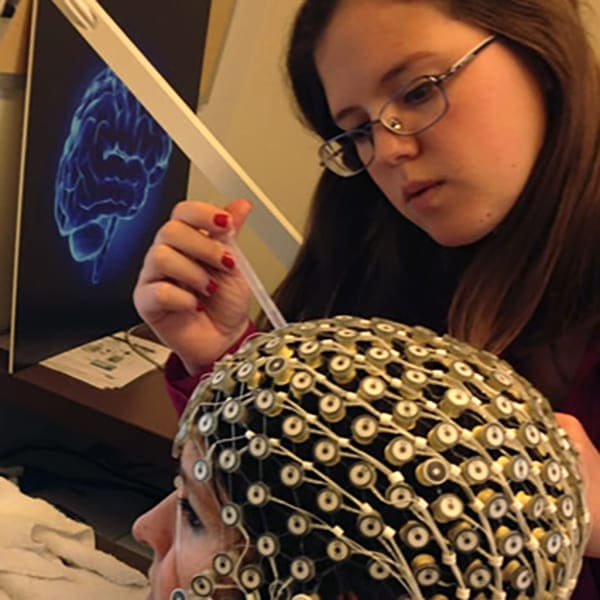 A researcher touches the monitoring equipment that is placed on a subject's head.