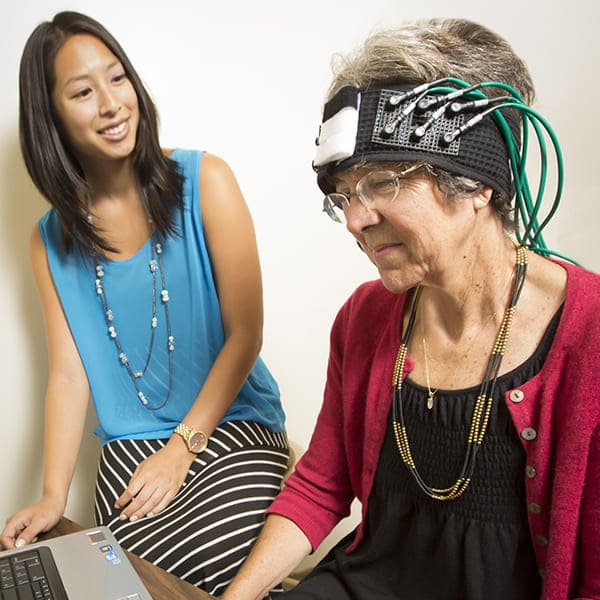 A researcher monitors a person who is wearing a monitoring equipment on their head.