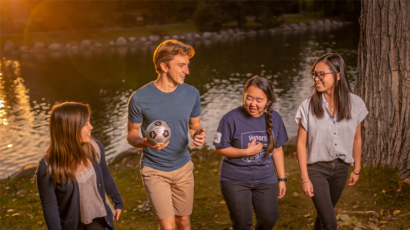 Four honors students standing near Manzanita Lake; one is holding a soccer ball.