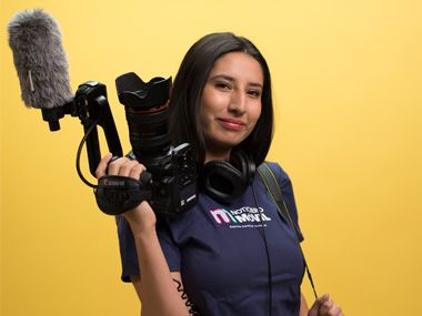 Student holds a video camera wearing a Noticero Móvil t-shirt.