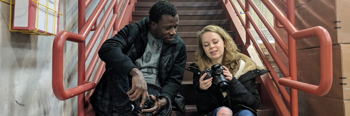 Two students sit on stairs looking at cameras.