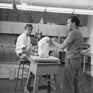 Joan Arrizabalaga is seated next to student sculptor Ron Moroni who is working on a piece in a studio (circa 1960). Photo credit: University Archives, University of Nevada, Reno.