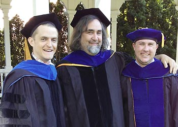 Three history graduate students in commencement regalia
