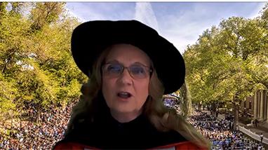 Professor wearing regalia speaking on quad