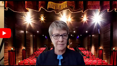 Debra Moddelmog on Zoom screen with empty theatre behind her