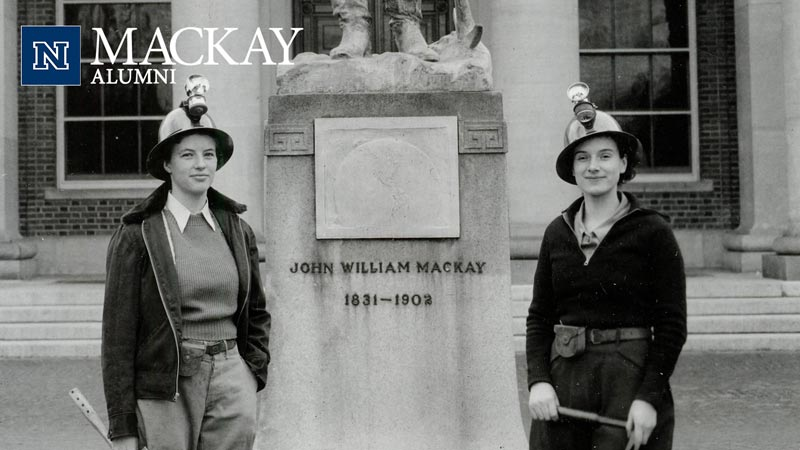 Old photo of two female miners standing in front of Mackay statue.