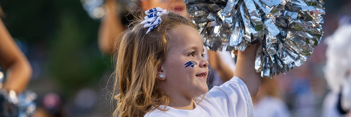 A child wears a blue Nevada Sport Wolf sticker on her cheek and cheers with a silver pom-pom with members of the University of Nevada, Reno dance team.