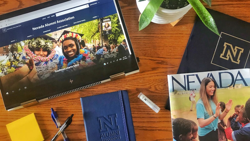 A desk showing an iPad with the Alumni website, a Nevada Silver & Blue magazine and other University of Nevada, Reno branded items