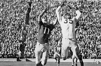 End Horace Gillom of the University of Nevada, Reno battles for a pass in a football game against St. Mary's University, at a packed Kezar Stadium.
