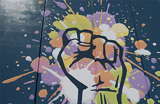 A painted mural of a hand in a fist, with splotches of pink, orange, yellow and green on the hand and surrounding portion of the mural.