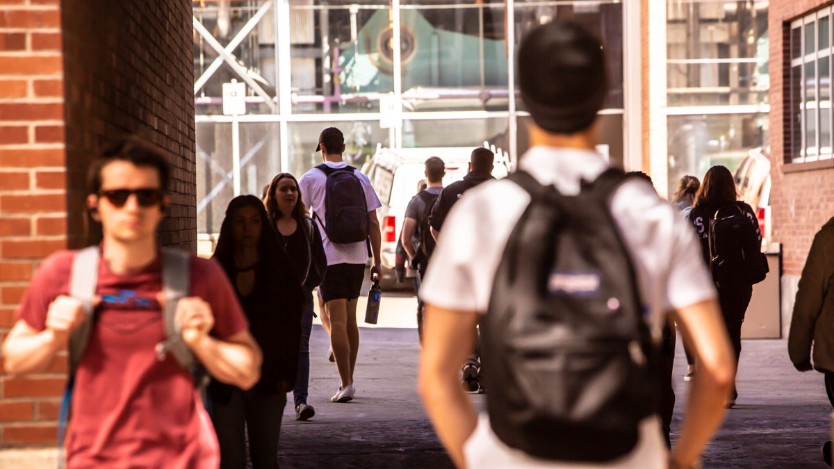 Students walk under a pedestrian walkway on campus, many wearing backpacks