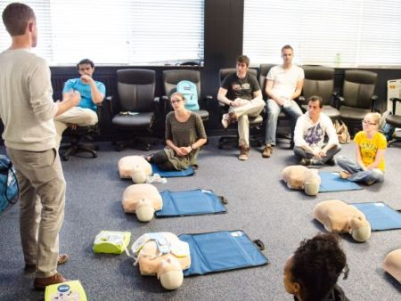 An EH&S personnel conducting a CPR training class in a room with participants