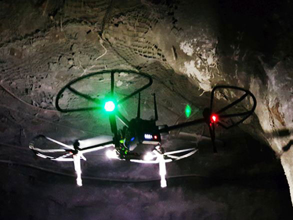 A drone with a bright green light flying around in a dark mining tunnel