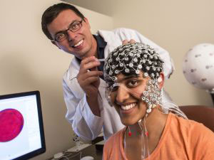 A researcher attaching headgear with electrodes to a research subject for a neuroscience experiment
