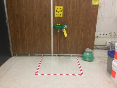 An eyewash station with safety tape marking an area on the floor around it