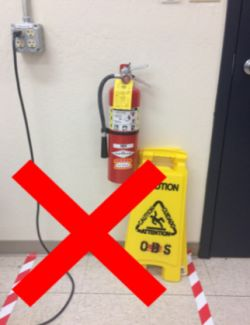 A fire extinguisher which has been unsafely blocked by a sign and a tripping hazard