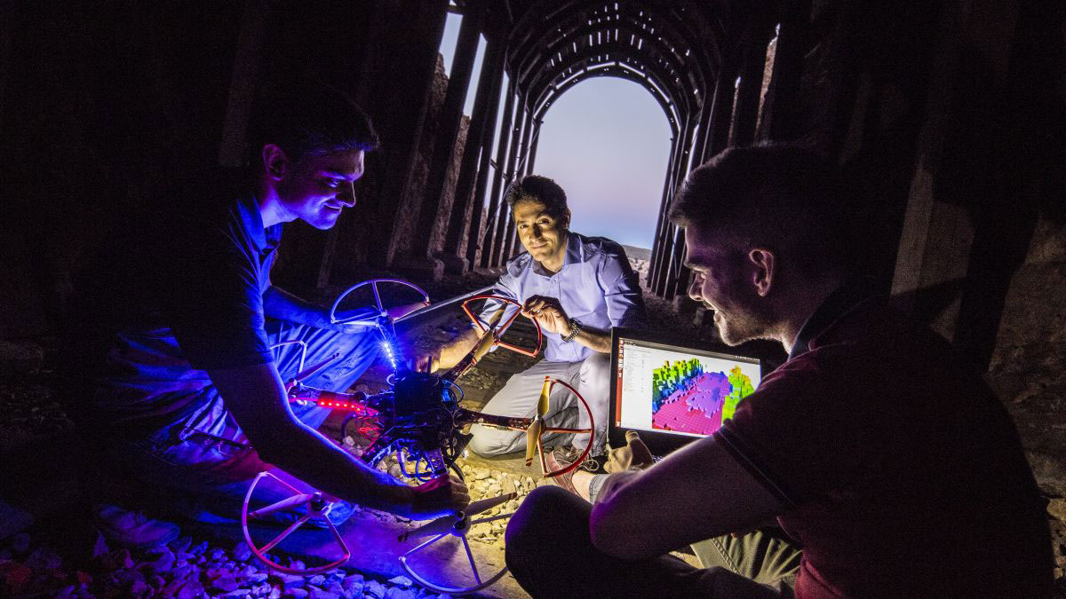 Three researchers in a dark mining tunnel, illuminated by a laptop and a flying drone