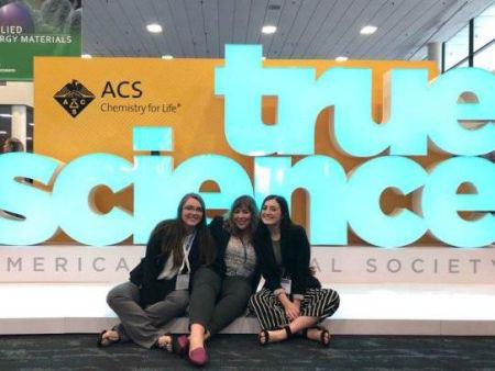 "Three students sitting in front of a sign reading ""true science"" at the American Chemical Society conference"