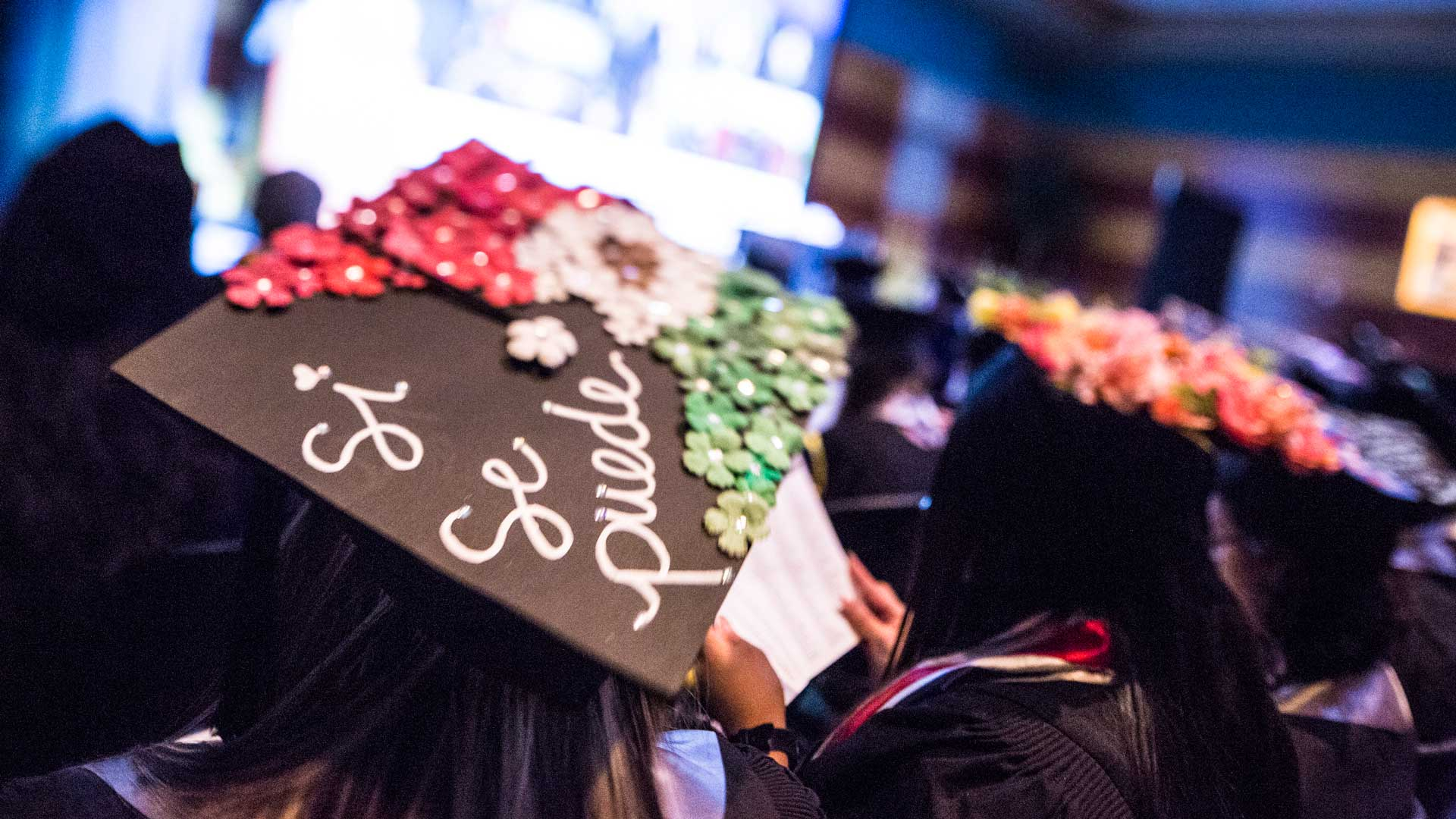 """Students sit in graduation attire at commencement with one mortar board in focus with the words """"Si Se Puede"""" written on it."""