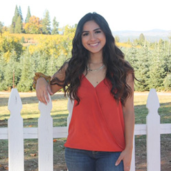 Angela Ramirez poses in a red shirt and jeans in front of a white picket fence with grass and trees in the background.
