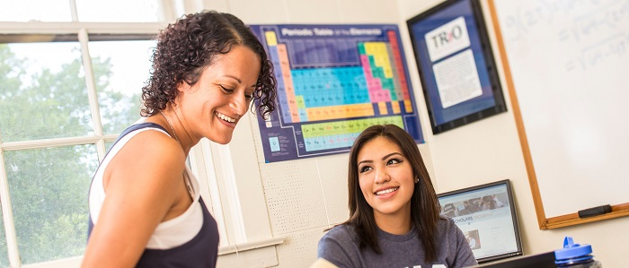 Two TRiO students study together in front of periodic table