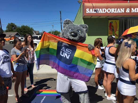 Alphie holding a Pride flag