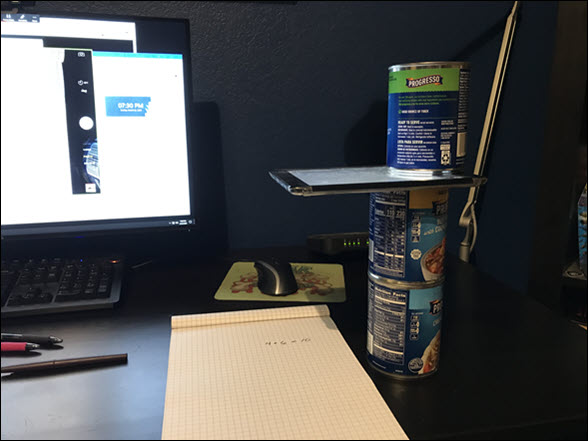 Desk showing a makeshift document camera consisting of 3 soup cans and an iPad. The soup cans are stacked and the iPad is placed between the top two cans with the camera aligned over a notepad.