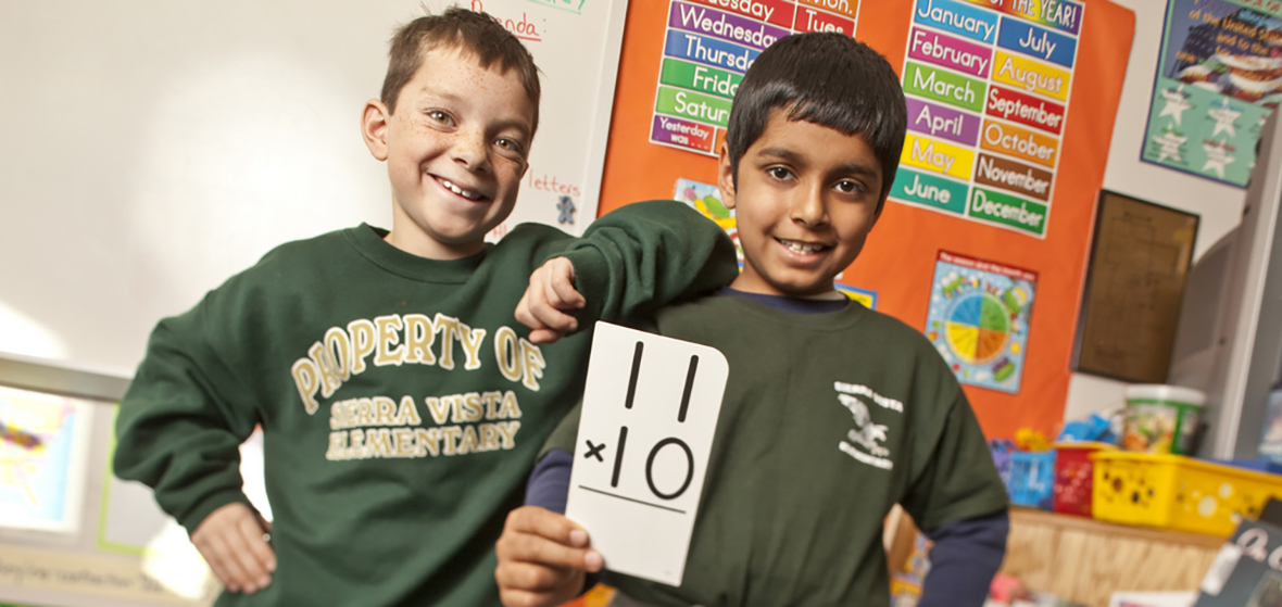 Two elementary schoolers smiling and holding up a math flash card