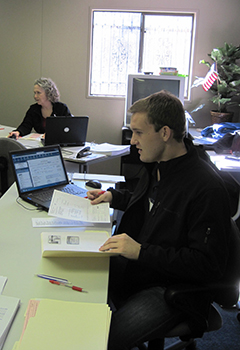 Colby Cross, an accounting student works at a table with a computer and papers