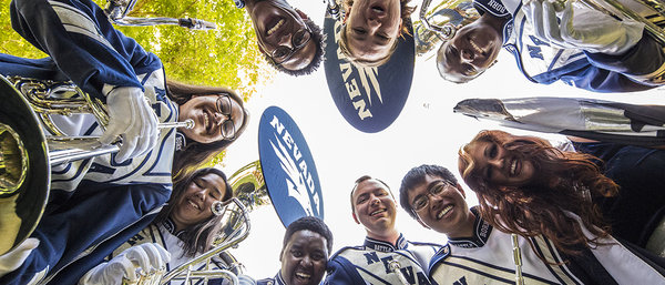 Members of the marching band in full silver and blue uniforms looking down into the camera