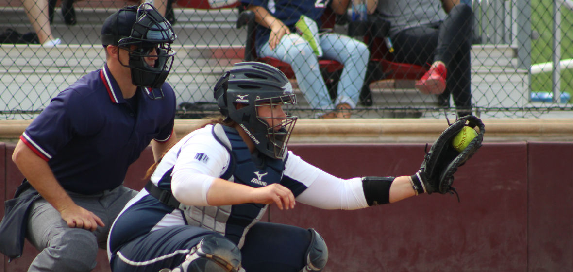 Amanda Nicholas playing catcher in a softball game with a ball in her glove.