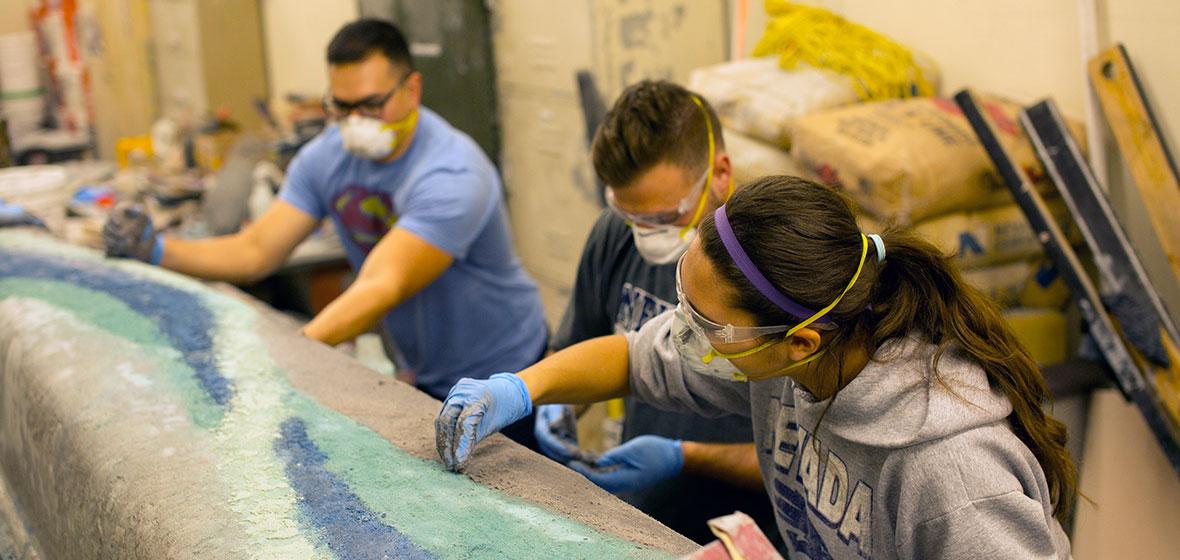 Engineering students work on concrete canoe.