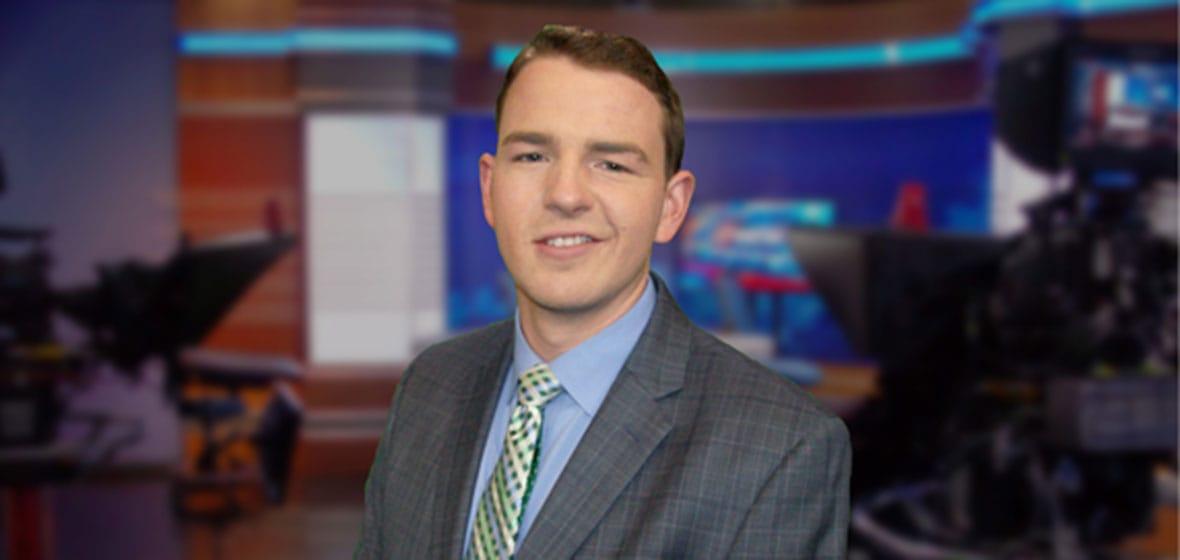 Man poses inside a news studio.