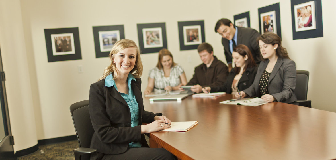 Business faculty and students meeting around conference table