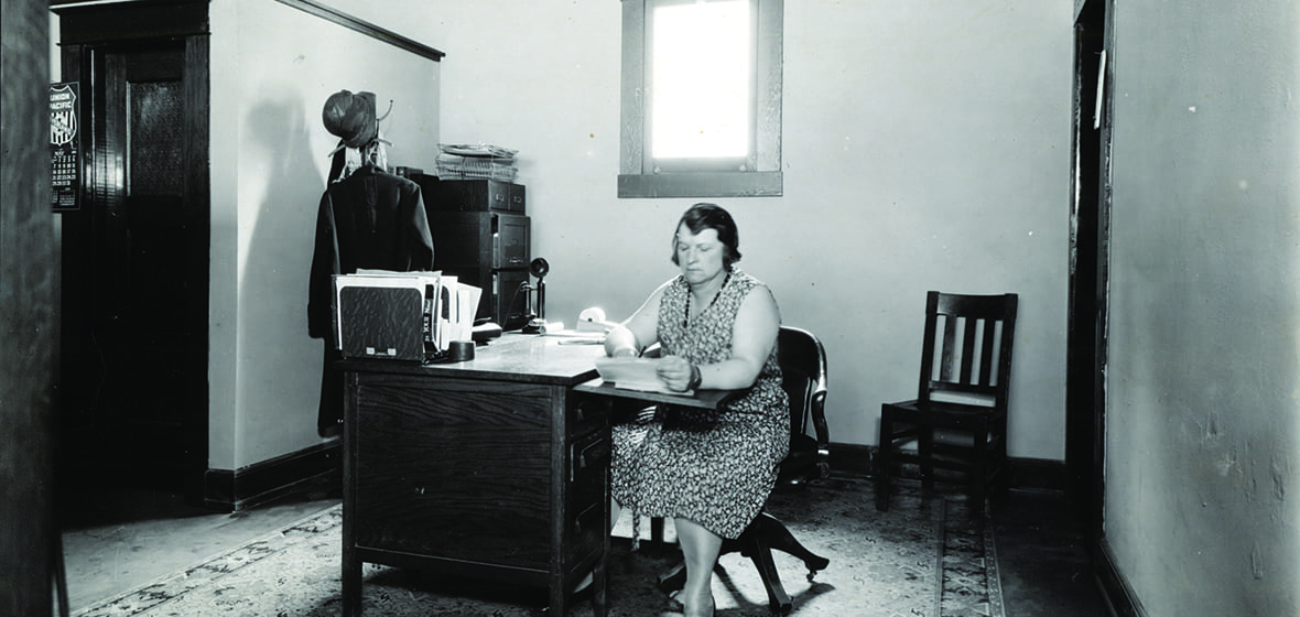 Photograph of an unidentified woman working at a desk in May 1929.