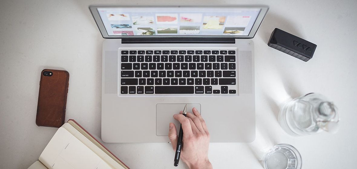 A hand can be seen typing on a laptop