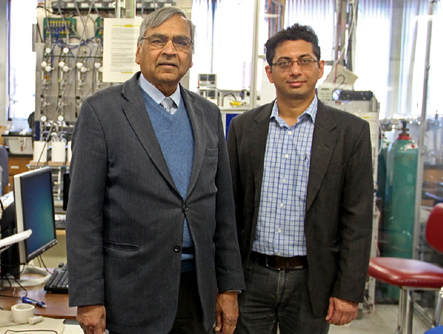 Two professors standing behind machines in a lab.