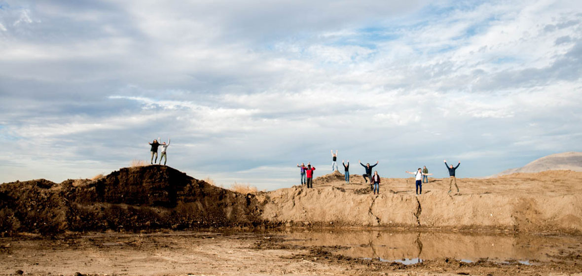 Students pose for a photo on top of a large dirt hill